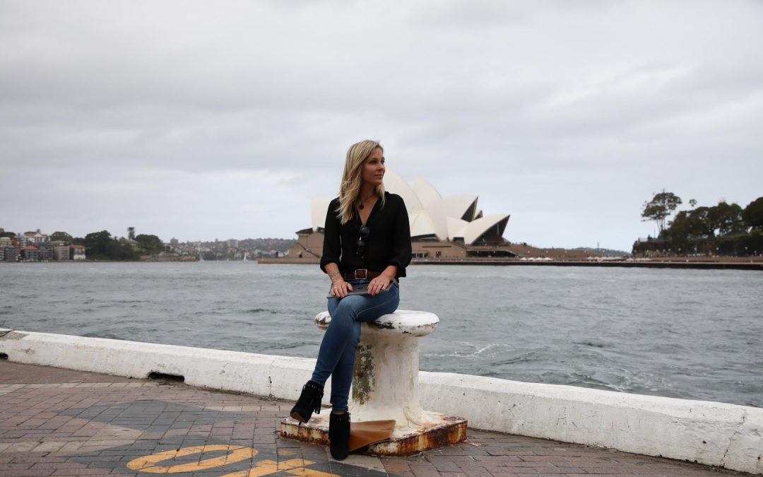 Woman wearing long sleeved top and jeans sitting near the edge of a brick docking station with the Sydney Opera House in the background.