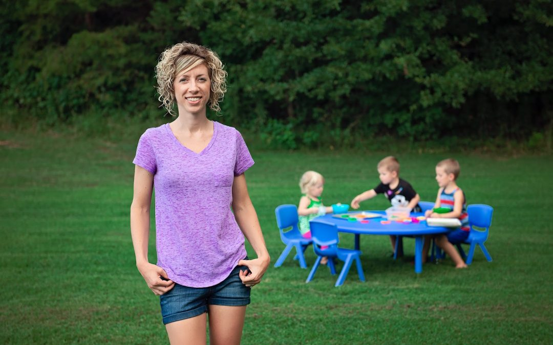 Blonde woman with short hair and purple shirt stands in the backyard with three children sitting and playing at a plastic table and chairs set.